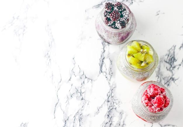 Chia pudding met bessen, frambozensaus, kiwisaus, bramensaus en bevroren frambozen