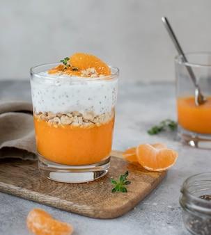 Chia-yoghurt met mandarijn en persimmon in een glas, gezond ontbijt.