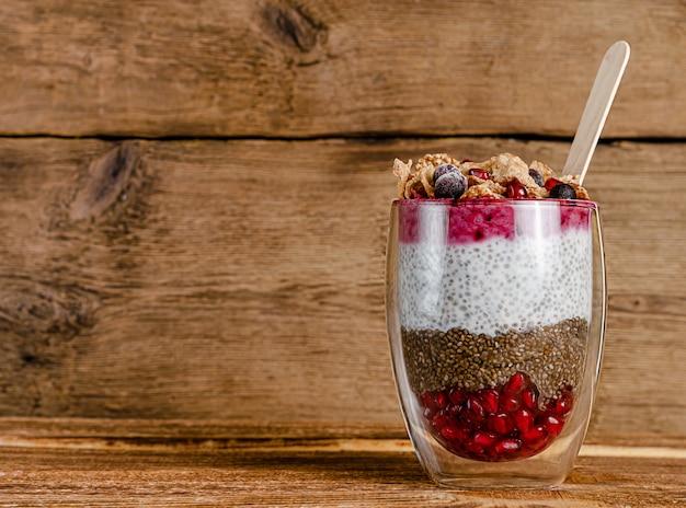 Chia yoghurt pudding met granen vlokken, bessen en granaatappel zaden op rustieke houten muur. kopieer ruimte
