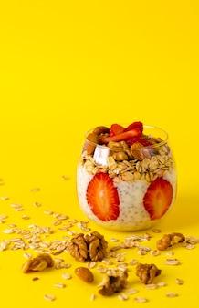 Chia yoghurtpudding met aardbeien, havermout en noten in een glas op geel