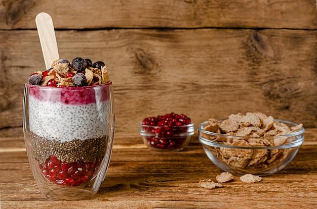 Chia-yoghurtpudding met graanvlokken, bessen en granaatappelpitjes. superfood concept. kopieer ruimte