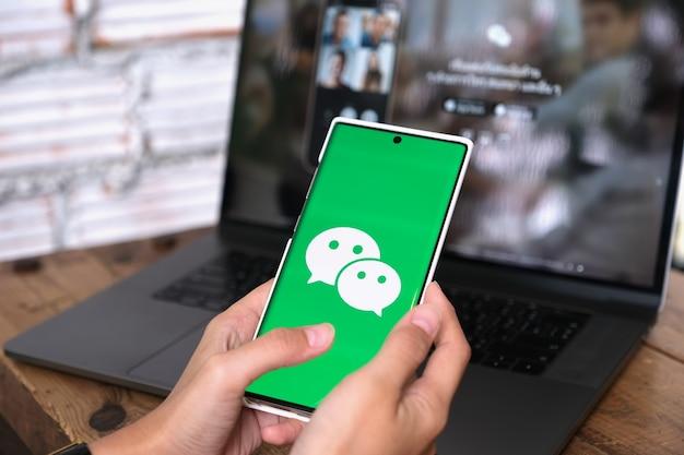 Chiang mai, thailand - 06,2021 juni: een vrouw houdt smartphone mobiel met wechat-app op het scherm. wechat is een chinese multifunctionele app voor berichten, sociale media en mobiele betalingen.