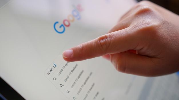 Chiang mai, thailand - 30 maart 2020: een vrouw die op zoek is naar informatie over covid-19 op google application.