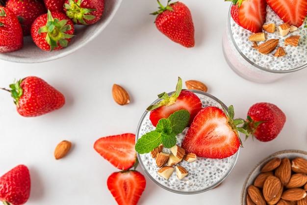 Chiapudding in glazen met verse aardbeien, amandelen en munt op witte ondergrond voor veganistisch ontbijt