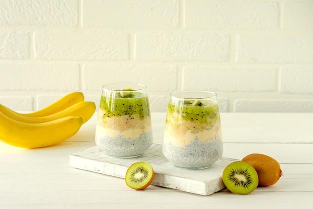 Chiazaadpudding met kiwi, banaan en mango. gezondheid detox ontbijt in glazen op witte achtergrond.