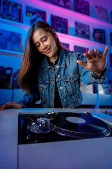 Chica dj latina mezclando muziek en una tienda de discos con un tornamesa y discos de vinil