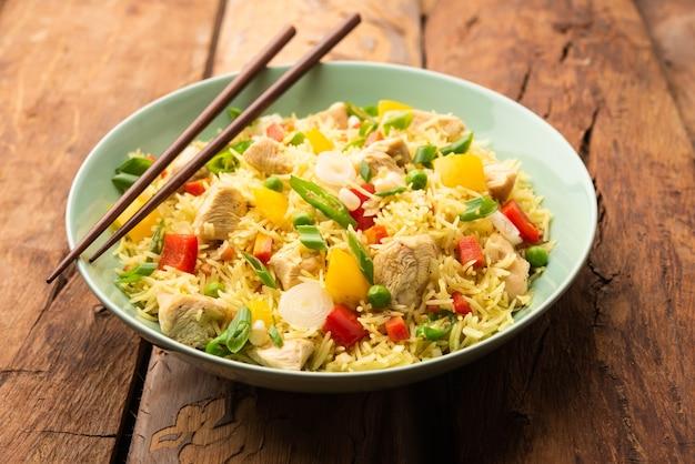 Chicken fried rice is een populair indiaas chinees of indo-chinees straatvoedsel dat wordt geserveerd in een bord met eetstokjes