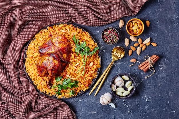 Chicken kabsa - zelfgemaakte arabische rijst met geroosterde amandelen van kippenkwart, rozijnen en knoflook op een zwarte plaat op een donkere betonnen achtergrond
