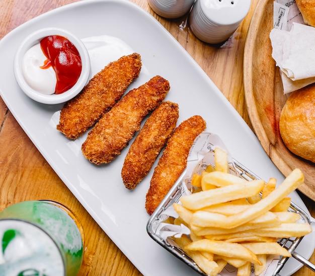 Chickensticks met frietjes ketchup mayonaise zijaanzicht