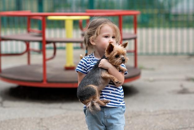 Chid knuffelt een yorkshire terrier-hond stevig op de speelplaats kind met hondenconcept