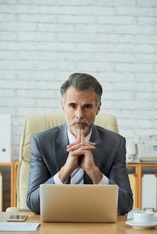 Chief executive officer werkt op laptop met vastberaden blik op de camera