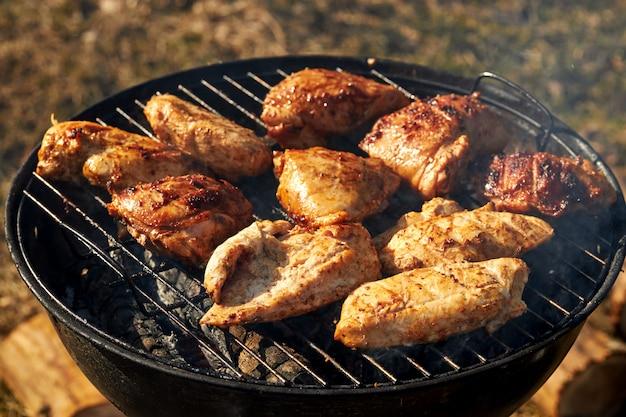 Chiken barbecue op een grill die de zomertijd van de open vuurlente roosteren