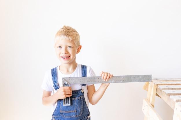Child builder meet een witte muur met een bouwliniaal