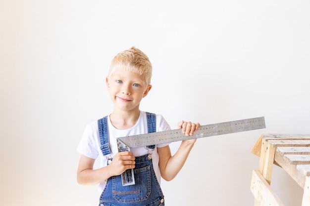 Child builder meet een witte muur met een constructie liniaal, constructie en reparatie concept