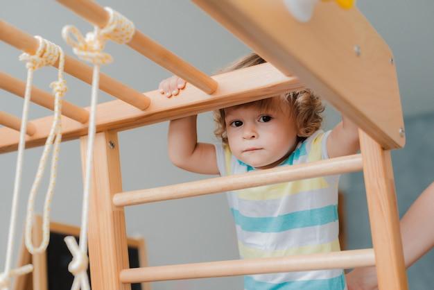Child houdt zich bezig met het houten sportcomplex voor kinderen thuis.