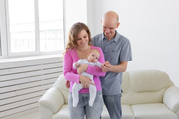 Childgood, ouderschap, mensen concept baby op handen van ouders op een witte muur.