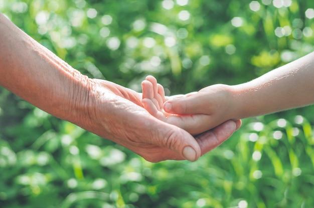 Childs hand en oude rot grootmoeder