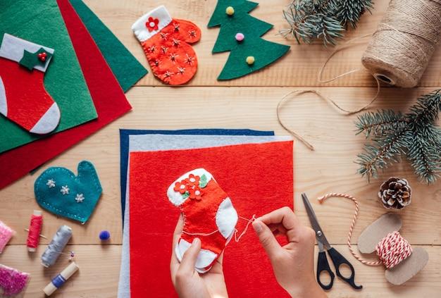 Childs hand met handgemaakte kerst vilten kous