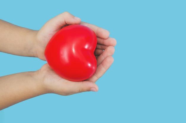 Childs handen met rood hart op blauwe achtergrond
