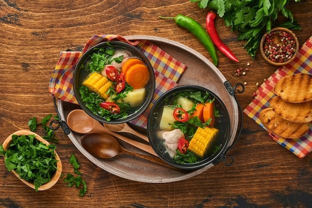 Chileense vleessoep met pampkin, maïs, verse koriander en aardappelen op oude houten tafel achtergrond. cazuela. latijns-amerikaans eten.