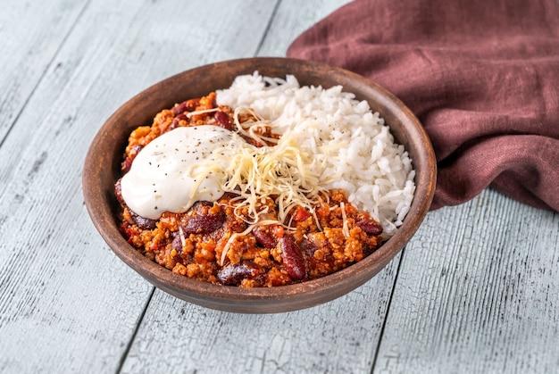 Chili con carne geserveerd met rijst, geraspte kaas en tortillachips