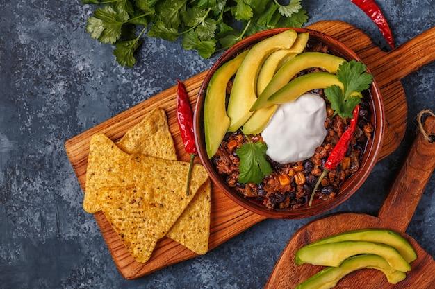Chili con carne in kom met avocado en zure room