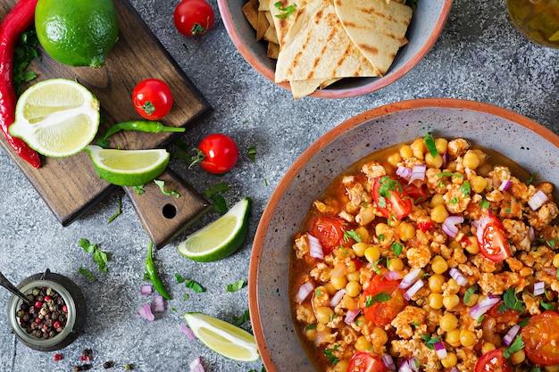 Chili con carne van kalkoen met kikkererwten geserveerd met nachos. chili met vlees, nacho's, limoen, hete peper. mexicaans / texas traditioneel eten. bovenaanzicht