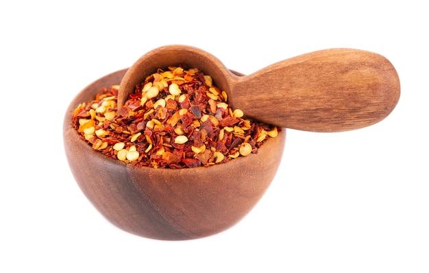 Chili en paprika in houten kom en lepel, geïsoleerd op wit.