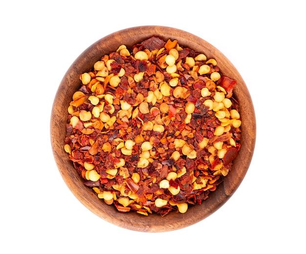 Chili en paprika in houten kom, geïsoleerd op wit.