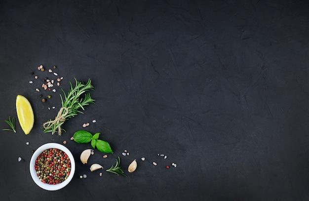 Chili, knoflook, olie en kruiden op zwarte achtergrond
