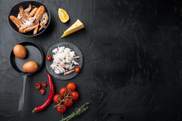 Chili krab zijdeachtige omlette ingrediënten ingesteld, op zwarte achtergrond, bovenaanzicht plat lag, met copyspace en ruimte voor tekst