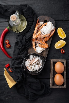Chili krab zijdeachtige omlette ingrediënten ingesteld, op zwarte houten tafel achtergrond, bovenaanzicht plat lag