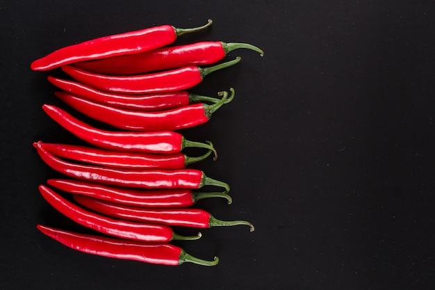 Chili pepers bovenaanzicht met kopie ruimte op zwart oppervlak