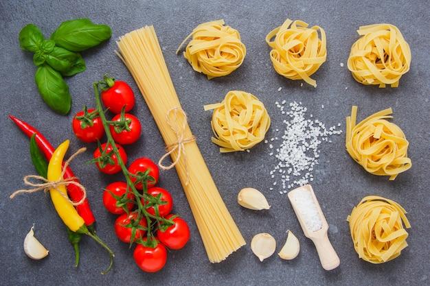 Chili pepers, een tros tomaten, zout, zwarte peper, knoflook, bladeren en spaghetti en tagliatelle pasta op een grijze ondergrond. bovenaanzicht.