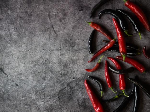 Chili peulen van rode en zwarte peper op donkere betonnen ondergrond