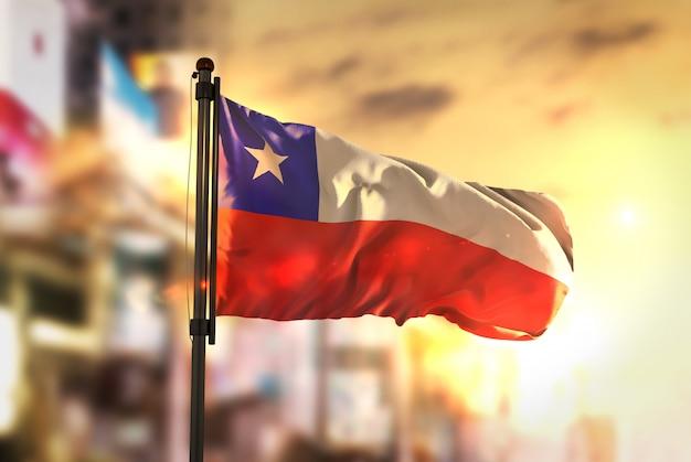 Chili vlag tegen stad wazige achtergrond bij zonsopgang achtergrondverlichting