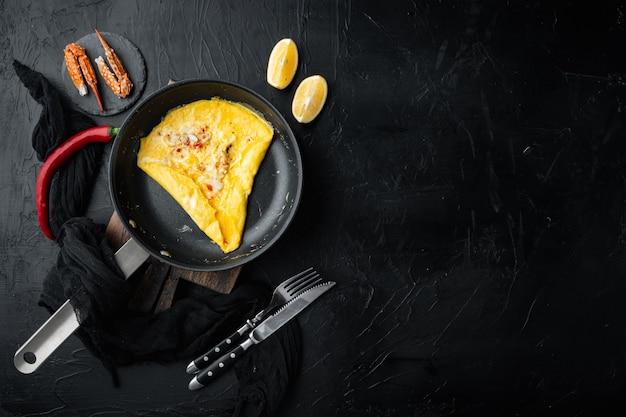Chilikrab zijdeachtige omlette, op koekenpan, op zwarte achtergrond, bovenaanzicht plat lag, met copyspace en ruimte voor tekst