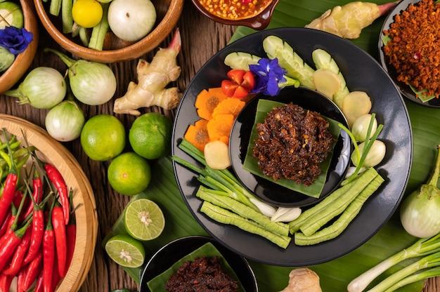 Chilipasta wordt geserveerd op bananenbladeren op een bord met kousenband, limoen, chili en aubergine.