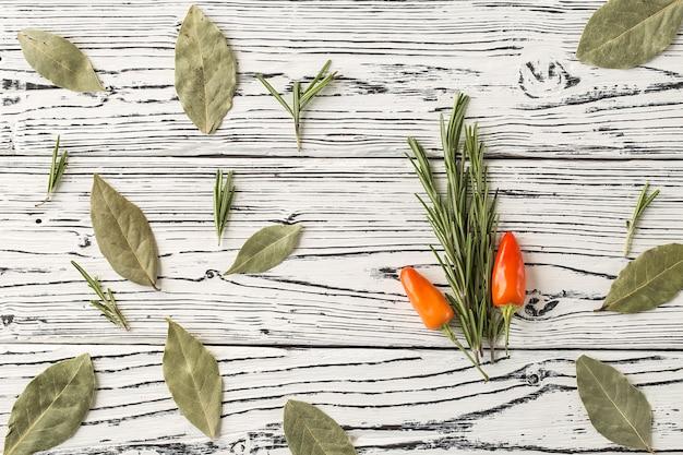 Chilipeper en rozemarijntwijgen met laurierbladeren op houten t
