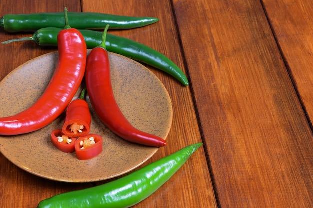 Chilipeper, evenals hun plakjes, liggen op een bruine schotel op een achtergrond van een houten tafel.