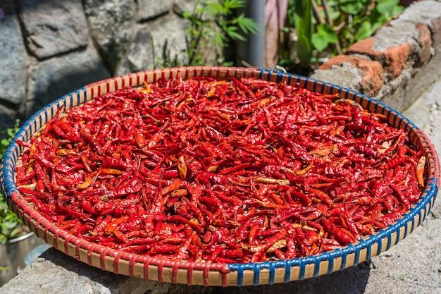 Chilipepers drogen op de zon in de dorsmand. stock foto.