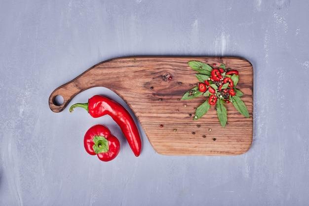 Chilipepers en kruiden op een houten bord.