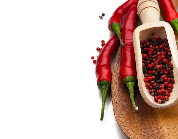 Chilipepers en peperkorrels in houten lepel