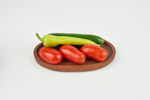 Chilipepers en tomaten op een houten bord op het wit.