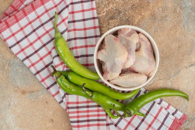 Chilipepers met onvoorbereide kippenpoten op tafellaken