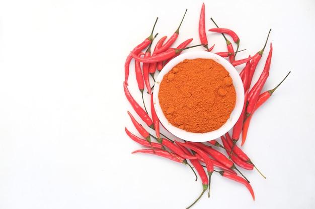 Chilipoeder en rode paprika's op witte achtergrond