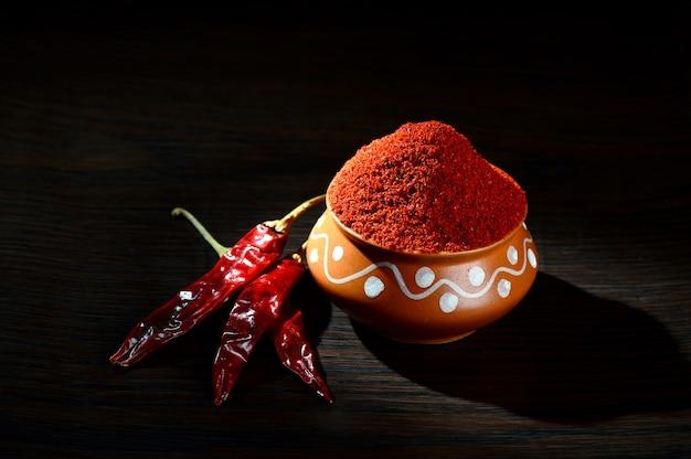 Chilipoeder in een aarden pot met rode spaanse peper op donkere houten