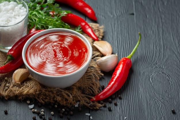Chilisaus en paprika op donkere houten ondergrond
