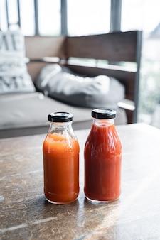 Chilisaus en tomatenketchup op een fles op de koffieachtergrond