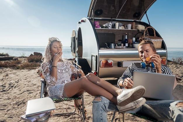 Chillen en roken. slanke moderne stijlvolle vrouw met dreadlocks koelen rookvrije sigaret zit in de buurt van haar man